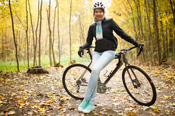 Photo of girl in helmet, jeans next to bicycle in autumn park