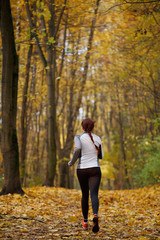 Picture from back in full growth of woman running along forest