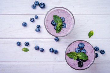 healthy smoothie or shake with fresh blueberries on a white wooden  background, top view