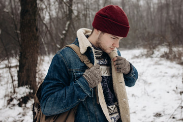 stylish hipster traveler with backpack posing in winter snowy forest. wanderlust and adventure concept with space for text. atmospheric moment. fashionable look