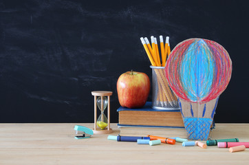 Back to school concept. hot air ballon and pencils in front of classroom blackboard.