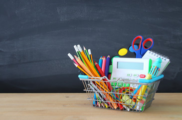 Shopping cart with school supply in front of blackboard. Back to school concept.