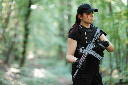Cute young woman with rifle in the forest