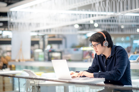 Young Asian business man listening to music by headphones while working with laptop computer in co working space. freelance or digital nomad lifestyle in urban workspace concepts