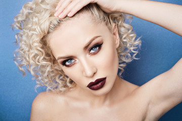Portrait of beautiful, fasionable and stylish model girl with amazing blue eyes, curly blonde hair and with professional bright makeup isolated at blue backgroung at studio