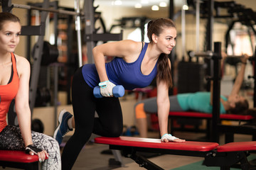 young women having workout in gym with dumbbells