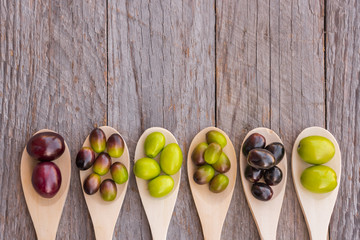 Different types of olives on wooden spoons Wall mural