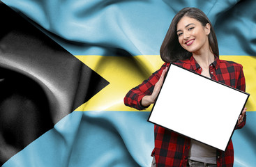 Woman holding blank board against national flag of Bahamas