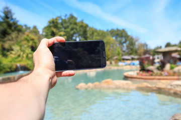Hand of a person holding the mobile with black screen and making a selfie in a paradisiacal pool on the beach