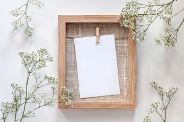 A wooden frame with a white mockup card and white flowers all around