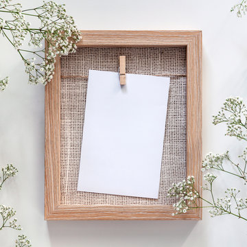 Wooden frame on a white background with card mockup and white field flowers around