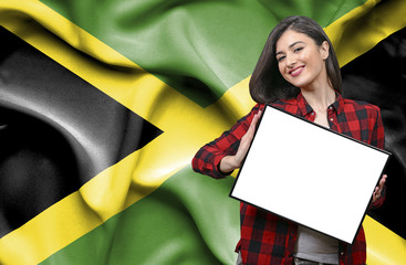 Woman holding blank board against national flag of Jamaica