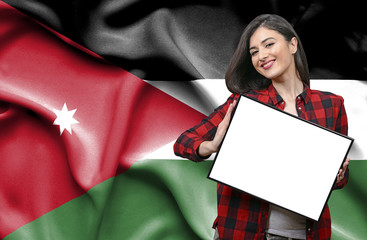 Woman holding blank board against national flag of Jordan