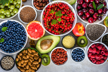 Table with healthy food assortment, fruit, nuts, seeds and various berries, superfoods selection, vegan diet concept