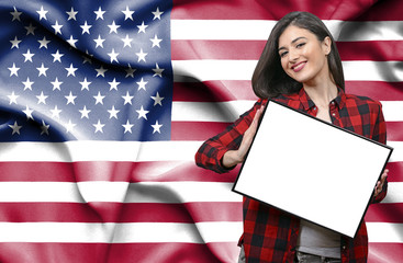 Woman holding blank board against national flag of United States of America