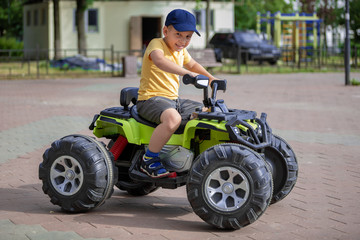 Portrait of a happy child on an ATV. The boy drives a car in an amusement park