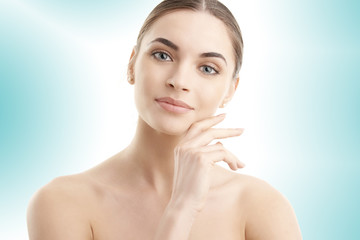 Portrait of a beautiful young woman with naked shoulders smiling while posing at isolated light blue background. Face beauty skin care. Natural make up