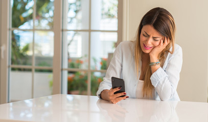 Depressed and sad woman crying using smartphone at home