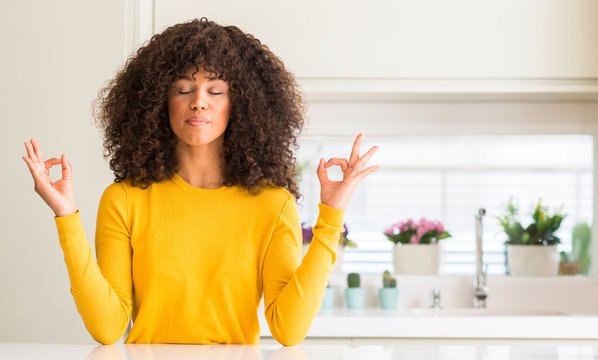 African american woman wearing yellow sweater at kitchen relax and smiling with eyes closed doing meditation gesture with fingers. Yoga concept.