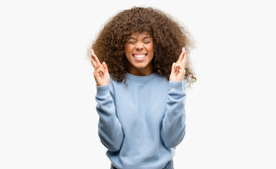 African american woman wearing a sweater smiling crossing fingers with hope and eyes closed. Luck and superstitious concept.