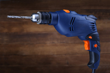 Electric drill on wooden background