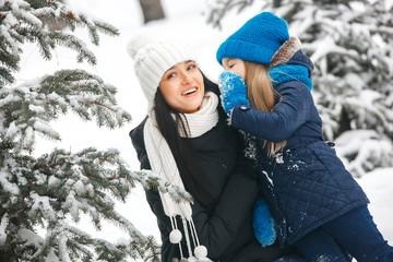 Little girl whispering her mother her christmas wish