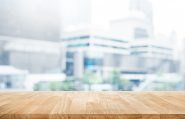 Wood table top on blur white glass window background form office building.For montage product display and design key visual