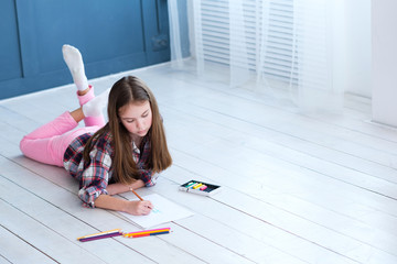 kid drawing hobby. childhood moments. little girl lying on the floor and creating a picture with pencils.