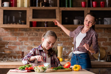 healthy family eating lifestyle. mom and daughter preparing vegetable salad.