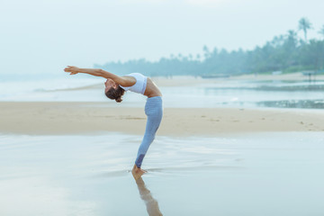 Caucasian woman practicing yoga at seashore of tropic ocean