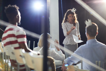 Princess businesswoman pointing at one of colleagues from audience during stage repetition