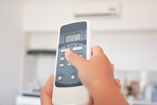 children's hand turns on the air conditioner using the remote control.