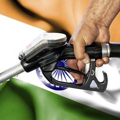 Gasoline consumption concept - Hand holding hose against flag of India