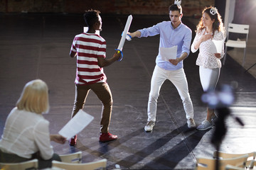 Two young princes fighting with paper swords for heart of princess during stage repetition