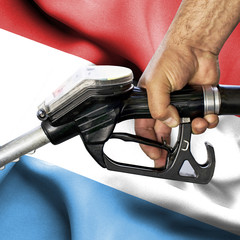 Gasoline consumption concept - Hand holding hose against flag of Luxwmbourg