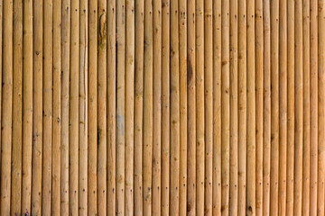 Close up of textured yellow privacy bamboo screen fence, made from natural organic materials