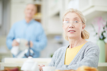Blond senior woman in eyeglasses looking at you with her husband taking care in the kitchen on background
