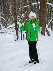 Beautiful girl in ski suit and white hat on skis in winter forest.