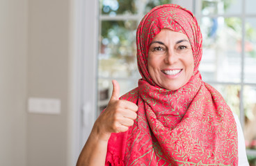 Middle aged muslim woman wearing hijab happy with big smile doing ok sign, thumb up with fingers, excellent sign