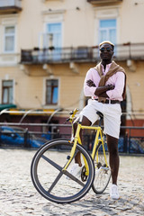 Handsome afro american man riding a bike in the street.