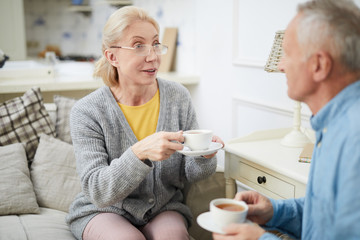 Casual senior woman with cup of tea sitting on sofa and talking to husband at home