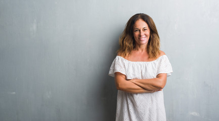 Middle age hispanic woman standing over grey grunge wall happy face smiling with crossed arms looking at the camera. Positive person.