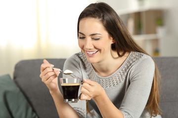 Girl holding a spoon with sugar and a coffee cup