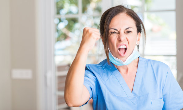 Middle aged doctor woman annoyed and frustrated shouting with anger, crazy and yelling with raised hand, anger concept
