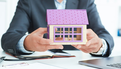 Businessman in suit holding house model. Loan or rent concept.