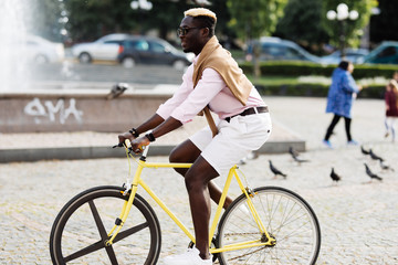 Handsome young Afro American man in casual clothes and sun glasses riding his bike and smiling