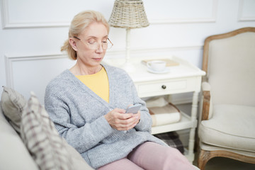 Senior female in domestic clothes sitting on sofa in living-room and reading messaging in her smartphone