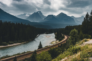 Scenic Morant's Curve with clouds and trees and mountains, Banff National Park, Alberta Canada