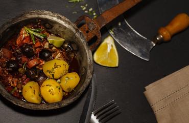 Italienische Fleischpfanne mit Oliven im Vintagestil präsentiert von oben