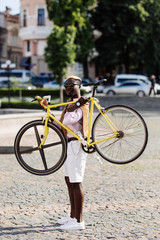 Handsome young Afro American man in casual clothes and sun glasses is holding a bike on the hands while walking on the street outdoors